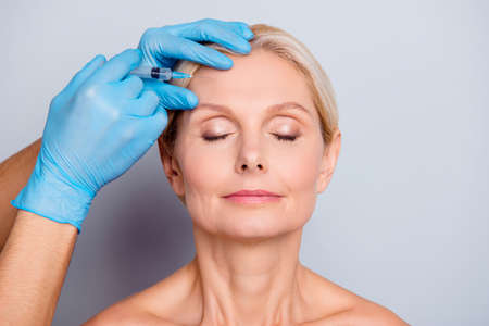 Portrait of calm serious aged woman with wrinkle keeping eyes close getting injection in forehead in professional clinic isolated on grey background