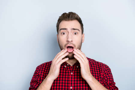 I don't like watching horror films! Close up portrait of unhappy sad upset fearful panicked clothed in red checkered casual shirt mad man touching his mouth isolated on gray background