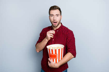 Wow! Portrait of scared frightened amazed surprised handsome attractive hipster voiceless guy watching the premier of film in the cinema, isolated on gray background