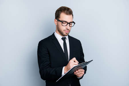 Portrait of confident concentrated self-assure handsome bearded smart clever guy writing information to the documents on clipboard in hid hands, isolated on gray background, copy-space