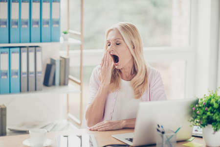 Pretty, attractive, stylish, modern, aged woman want to sleep, holding hand near open mouth, yawning with close eyes, sitting at desk in workplace Stock Photo