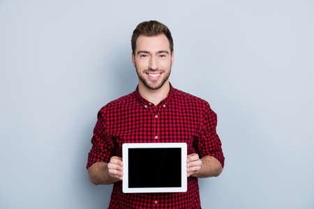 Portrait of cheerful glad confident excited professional guy showing ideal empty screen of updated upgraded tablet from brand new product line, isolated on gray background