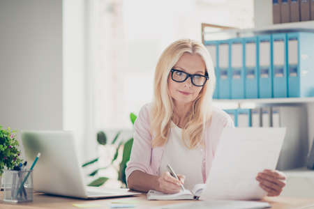 Confident, concentrated, busy, thoughtful, aged woman having paper in hand, looking at document and making noted in her notepad, sitting at desktop in work station 版權商用圖片
