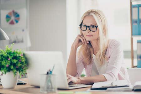 Nette, niedliche, selbstbewusste, charmante Schulleiterin mittleren Alters, die am Schreibtisch am Arbeitsplatz sitzt, Hand in der Nähe des Gesichts hält, Informationen auf dem Computer sucht und E-Mails abruft Standard-Bild
