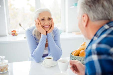 Portrait of charming attractive sweet cute lovely woman sitting at the table in kitchen, having mug with tea looking at man, spending, admire nice time together, listening her lover
