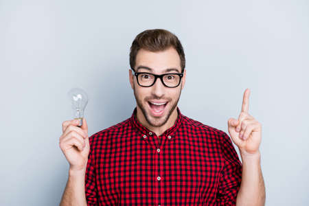 Yes! Genial ideas are the most obvious! Close up of thoughtful minded cheerful delighted handsome astonished amazed wondered guy holding light bulb, completed task, isolated on gray background