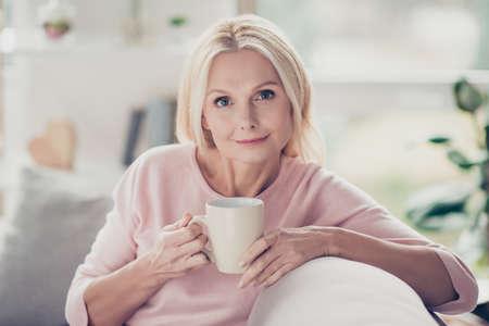 Moderne, stilvolle, kaukasische, gealterte Frau, die am Morgen eine Tasse Kaffee trinkt, auf dem Sofa im Wohnzimmer zu Hause sitzt und Kamera betrachtet Standard-Bild