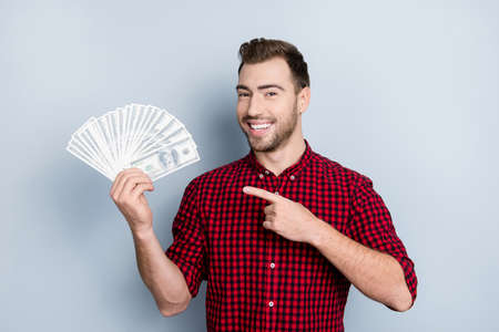 Portrait of handsome confident with toothy beaming smile smart rich wealthy friendly cheerful excited entrepreneur demonstrating many banknotes in hand with forefinger isolated on gray background 스톡 콘텐츠
