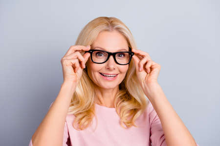 Portrait of cheerful positive charming attractive cute woman with wrinkle holding eyelets with two hands of glasses on her face looking at camera isolated on grey background