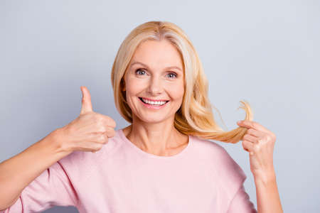 Portrait of glad pleased charming cheerful aged woman gesturing thumb up with finger showing smooth healthy perfect soft ends enjoying oil product lotion isolated on grey background