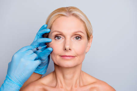 Portrait of calm serious charming aged woman with wrinkle getting injection in cheek in professional clinic hands in gloves making face contouring isolated on grey background Stockfoto