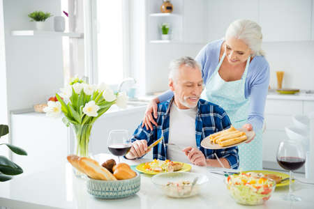 Beautiful attractive woman cooked appetizing dishes for her lover, standing, demonstrate plate with pancakes to handsome man, sitting in dining room, hug, embrace