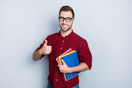 I recommend you to visit this course of English! Portrait of excited cheerful satisfied delightful handsome showing thumb-up and holding book, isolated on gray background