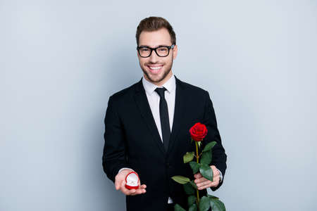 Will you marry me? I love you my darling, be my wife forever! Portrait of excited loving tender gentle cheerful man with rose and engagement ring making a marriage offer, isolated on gray background