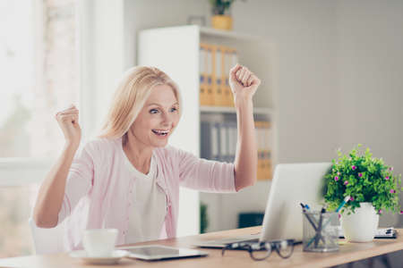 Attractive, stylish, modern, pretty, charming, aged woman looking at screen of computer with raised hands celebrating successfully completed work, project, presentation, sitting at desktop in work station