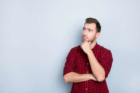 I'm confused don't know what to choose, where to go! Handsome attractive thoughtful bearded guy wearing checkered shirt with rolled up sleeves, pondering about weekends, isolated on gray background