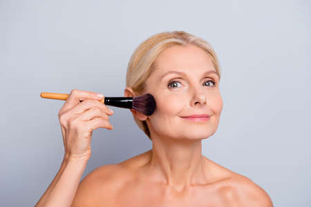 Portrait of charming woman with smooth soft perfect skin applying rouge with brush on cheek looking at camera isolated on grey background Foto de archivo - 103229027