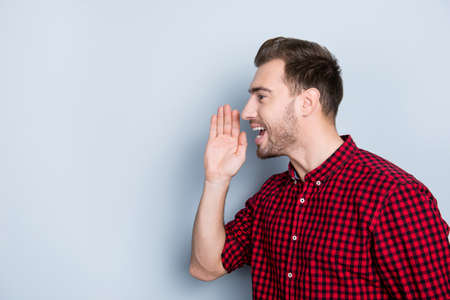 Half-faced side profile view portrait of excited delightful emotional cheerful screaming guy with stylish modern hairdo clothed in red checkered shirt outwear isolated on gray background copy space Stock Photo