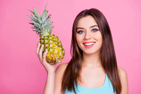 Summer Im waiting for you! Close up portrait of cheerful excited with toothy smile attractive flirty pretty tender lovely girl holding yellow delicious pineapple in hand, isolated on pink background 写真素材