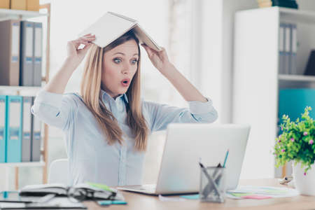 Portrait of astonished, shocked, attractive, childish, comic, funny woman with wide open eyes holding notepad like roof on her head, looking at screen of laptop
