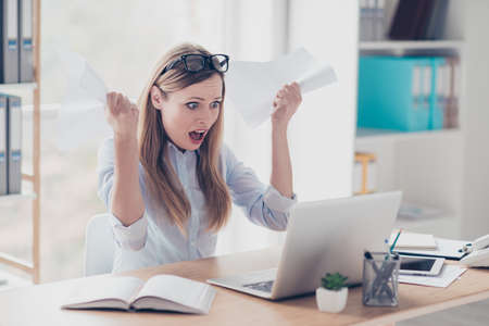 Portrait of attractive, shocked woman with wide open mouth looking at screen of computer holding papers in arms, with unbelievable, unexpected reaction sitting in workplace at desktop