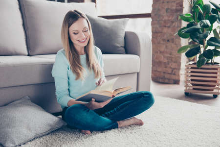 Portrait of attractive, pretty, smart, charming, cheerful, stylish woman sitting on the floor on carpet near sofa with crossed legs, reading her favorite book Фото со стока