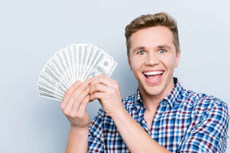 Bill casual career  income earn face emotion expressing happiness people person concept. Close up portrait of man excited cheerful rejoicing delightful guy demonstrating cash isolated gray background