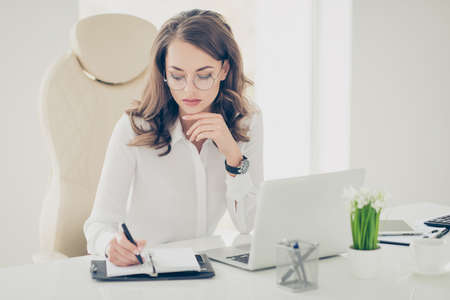 Portrait of charming pretty stylish trendy secretary sitting on armchair making notes, schedule in notepad writing down a date of conference, meeting, organizing her day, week