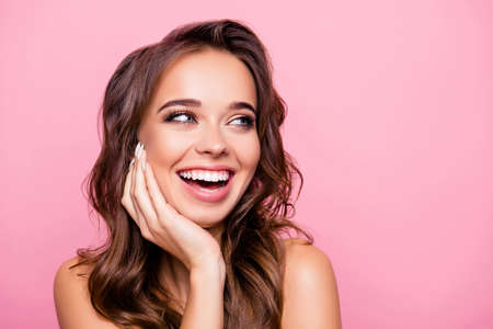 Aging, acne, pimples, wrinkles, oily, dry skin concept - close up portrait of pretty excited lady with wavy hairdo, holding palms on cheek, isolated on pink background