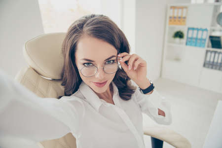 Self portrait of pretty, charming, joyful, positive, cheerful, trendy, stylish, brunette woman with hairdo shooting selfie on front camera holding eyelet of glasses on her face with hand