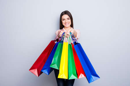 Portrait of pretty, charming, glad, positive woman giving many colorful packets front to the camera isolated on grey background, I bought for you these all gifts
