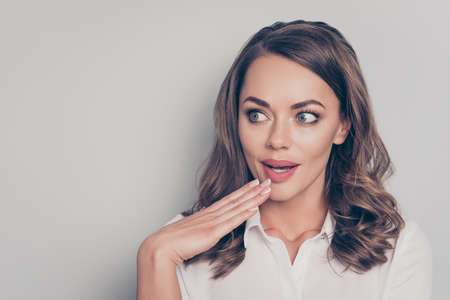 Oops! Portrait with empty place copy space of nice, cute, trendy, pretty, charming, pretty, surprised, positive, excited woman holding palm near lips looking to the side isolated on grey background