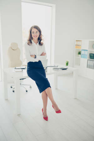 Portrait of pretty, charming, sexy, trendy, brunette, positive director, boss with curls, hairdo wearing stilettos shoes having her arms crossed looking at camera, modern interior