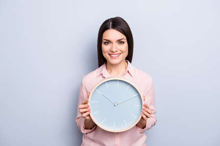 Its 10:10 oclock. Portrait of charming pretty positive cheerful woman having round clock in hands looking at camera isolated on grey background
