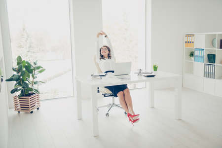Full-size portrait of pretty, charming, stylish, positive woman making stretching with raised hands up, close eyes, sitting on armchair in open space office enjoying timeout having fun, pleasure