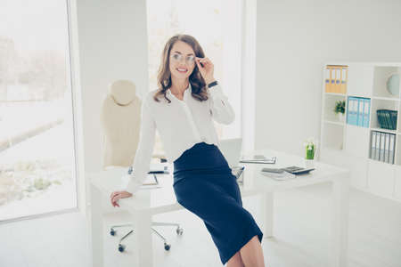 Portrait of pretty, trendy, charming, positive, brunette, cheerful lawyer with hairstyle holding eyelet of glasses on her face with hand looking at camera, open space modern office Standard-Bild