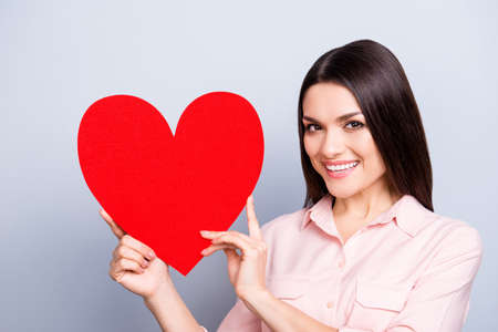 Portrait of lovely, sweet, charming pretty woman having gesturing big paper carton red heart near face looking at camera isolated on grey background