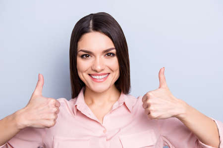 Portrait of pretty, charming, trendy, cute woman in classic shirt showing two thumbs up with fingers looking at camera isolated on grey background