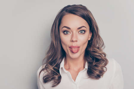 Portrait of nice, cute, trendy, pretty, charming, pretty, positive, crazy, comic woman with curls hairdo gesturing tongue out looking at camera isolated on grey background