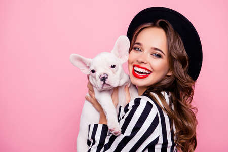 Charming, pretty girl with beaming smile and make up holding dog in hands near face, together looking at camera Stock fotó