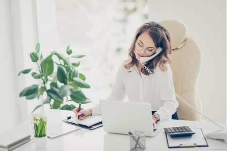 Portrait of concentrated, charming, smart, pretty, stylish hardworking accountant making notes in notebook, writing down a date of meeting speaking on phone with handset browsing typing on laptop