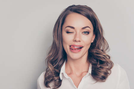 Close up portrait of nice, cute, trendy, pretty, charming, pretty, positive, crazy, comic woman gesturing tongue out blinking with one eye looking at camera isolated on grey background