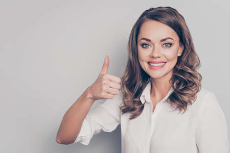 Portrait with copy space empty place of nice, cute, trendy, pretty, charming, pretty positive woman with curls showing thumb up with finger isolated on grey background Stock Photo