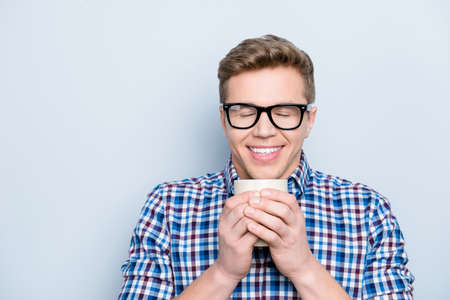 Aromatic university person delight pleasure concept. Close up portrait of rejoicing funny funky cheerful joyful cute lovely guy drinking fresh tasty coffee isolated on gray background copy-space