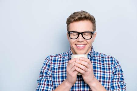 Aromatische Universitätsperson erfreuen Vergnügungskonzept. Schließen Sie herauf Porträt des Freuden des lustigen funky fröhlichen freudigen niedlichen reizenden Kerls, der frischen leckeren Kaffee trinkt, der auf grauem Hintergrundkopierraum isoliert wird
