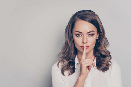 Shhh! Portrait with copy space empty place of nice, cute, trendy, charming, pretty, serious woman with curls hairdo showing silence sign with forefinger looking at camera isolated on grey background