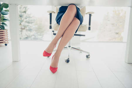 Cropped front view portrait bottom view of womans legs wearing black skirt red high heels shoes sitting leg by foot on chair in workplace, workstation having ideal stunning perfect thin tempting legs 写真素材