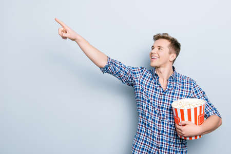 Profile side view portrait of surprised wondered astonished amazed handsome emotion expressing curious excited cheerful glad man pointing on copy space place empty isolated on gray background Stock Photo