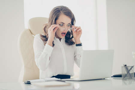 Terrified, impressed, surprised, sad, unhappy financier looking out glasses on her face holding eyelets with hands with wide open eyes mouth looking at screen of computer, having ruin of company
