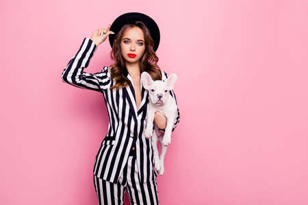 Attractive, charming, pretty girl in fashionable outlook, having dog under armpit, holding hat on her head, looking at camera, standing over pink background